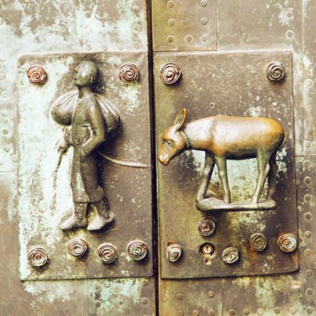 Tür der Ulrichskirche mit Bauer und Esel