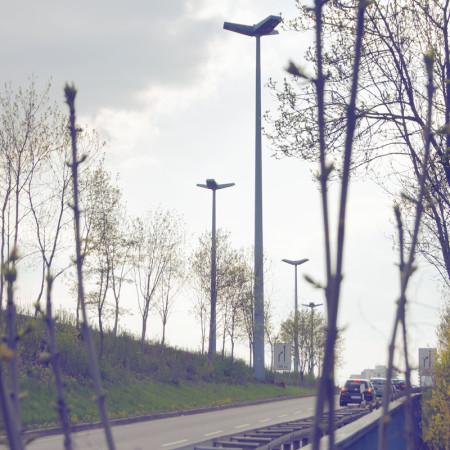Magistrale mit Zweigen von Busch und großen Straßenlampen