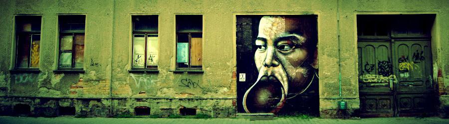 Graffitigesicht auf einer Tür (altes Gebäude)